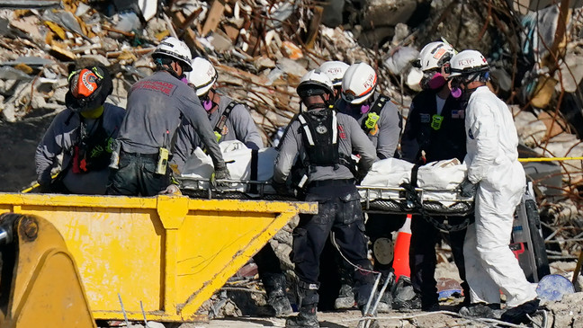 FILE - In this Friday, July 2, 2021, file photo, search and rescue personnel remove remains on a stretcher as they work atop the rubble of the Champlain Tower South complex in Surfside, Fla. (AP Photo/Mark Humphrey, File)